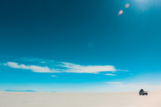 Красивый снимок неба с выцветшими облаками в яркий день с автомобилем в пустыне