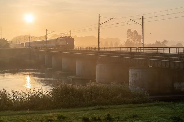 Красивый снимок поезда, проезжающего по мосту в солнечный день
