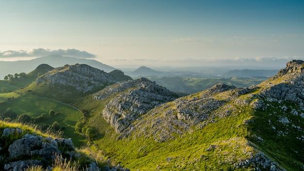 밝은 날 나무로 덮인 언덕과 절벽의 아름다운 샷
