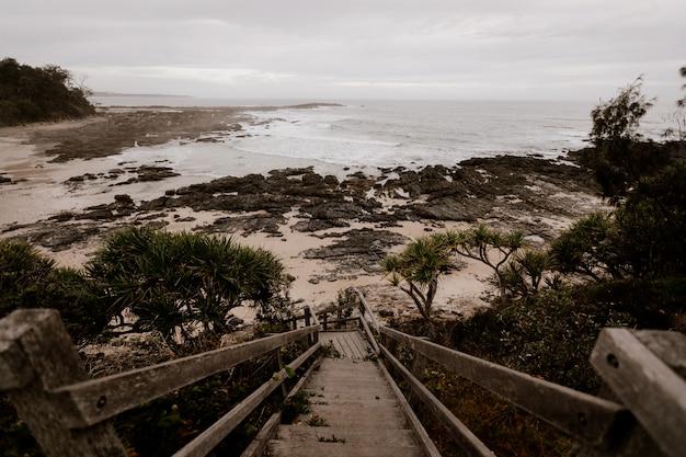 Красивая съемка деревянной лестницы к берегу около моря с облачным небом в предпосылке