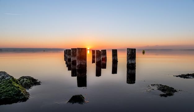 日没時に水の体に使い古された桟橋柱の美しいショット。壁紙に最適