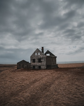 Beautiful shot of an old abandoned and half-destroyed house in a large brownfield under gray sky