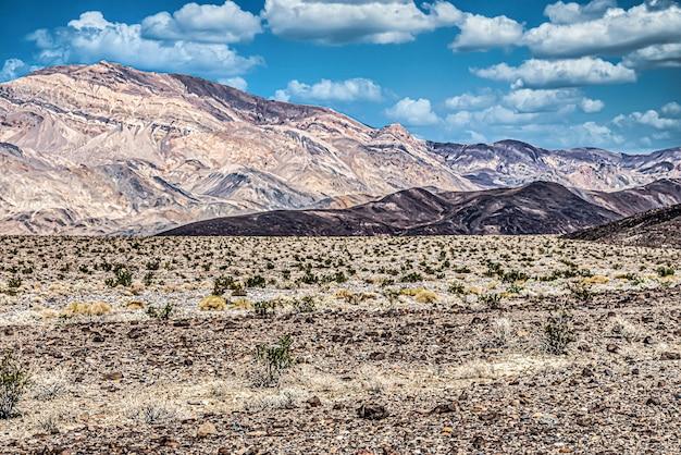 Bella ripresa di un campo aperto con alte montagne e un cielo blu nuvoloso