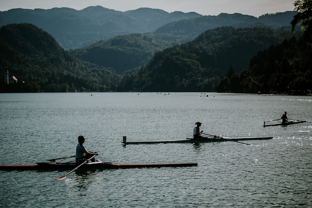 Beautiful shot of people riding boats on the water with forested mountains