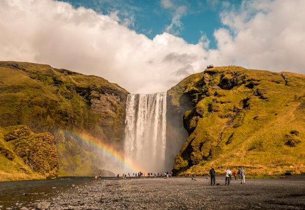 Beautiful shot of people standing near the waterfall with a rainbow on the side in skogafoss iceland