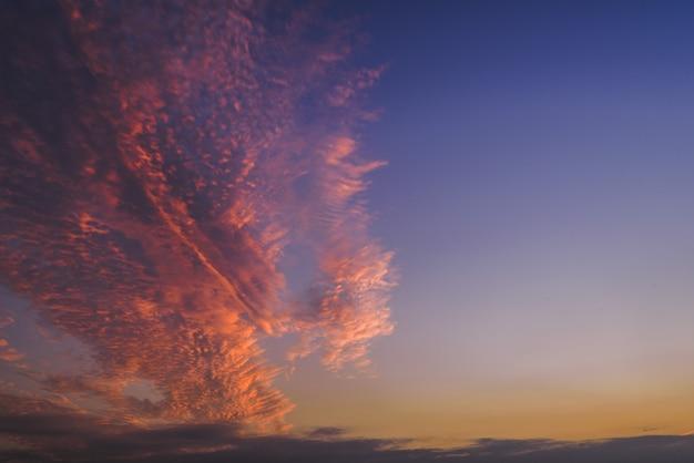 Bello colpo delle nuvole rosa e porpora nel cielo su chiaro fondo blu