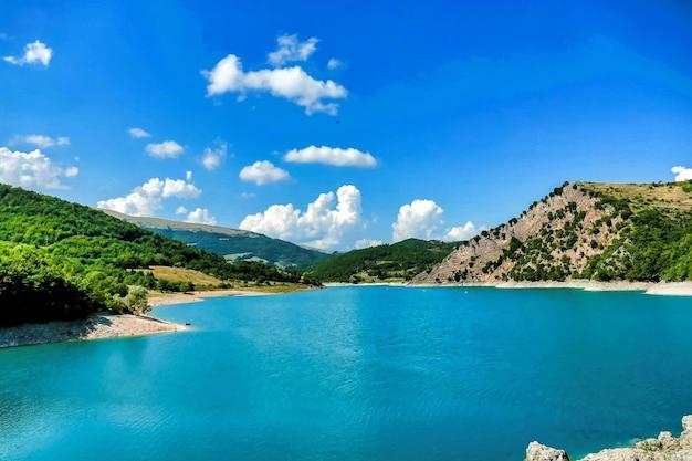 Bella ripresa di uno stagno circondato da montagne sotto un cielo blu in umbria, italia