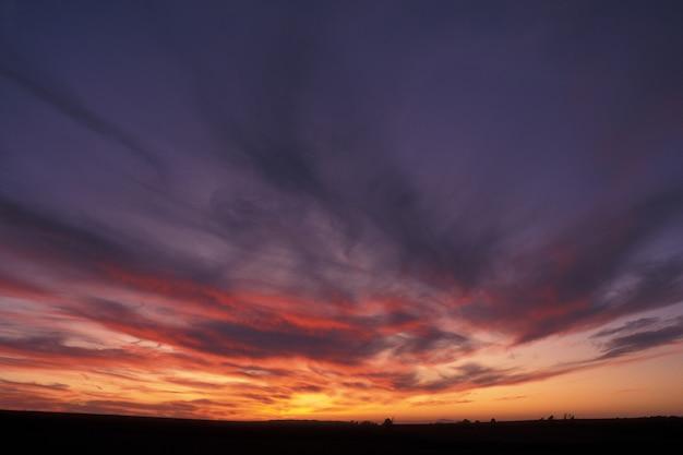 Bello colpo di un cielo porpora ed arancio con le nuvole al tramonto a guimaras, filippine