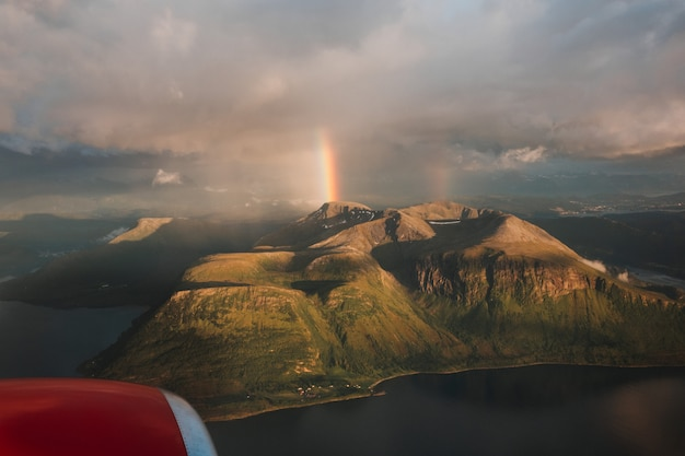 Beautiful shot of a rainbow above green mountains under a cloudy sky