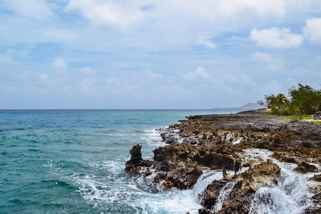 Beautiful shot of rocks on a seashore with a cloudy blue sky in the background