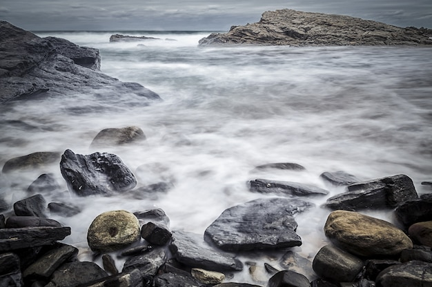 Beautiful shot of rocks in the seashore with a gloomy sky