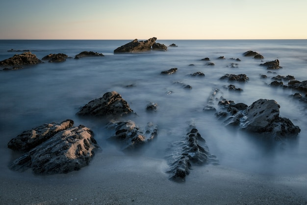 Beautiful shot of rocks in the seashore with a white sky in the background