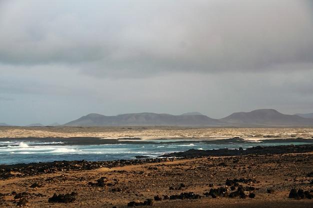 Bella ripresa di una spiaggia rocciosa durante la tempesta a fuerteventura. spagna