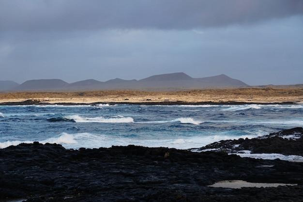 Bella ripresa della spiaggia rocciosa e delle montagne a fuerteventura, spagna