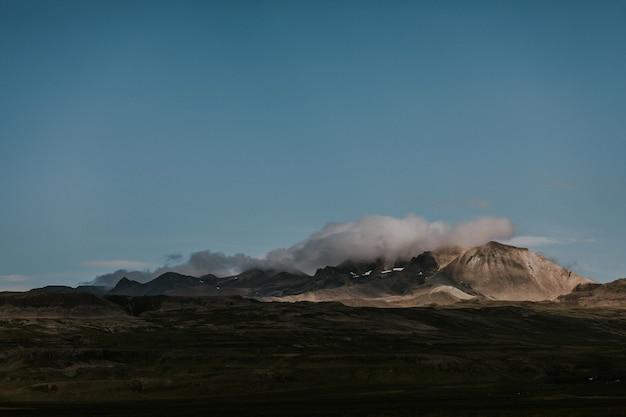 Bellissimo scatto di colline rocciose ricoperte di nuvole bianche in una terra verde