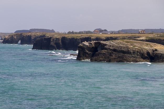 Bellissimo scatto di montagne rocciose bagnate dalle onde dell'oceano blu