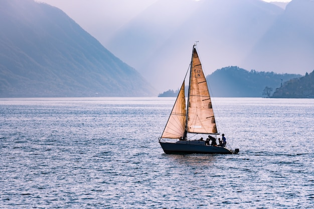Beautiful shot of a sailing boat travelling across the sea surrounded by mountains