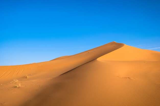 Beautiful shot of a sand dune with a clear blue sky