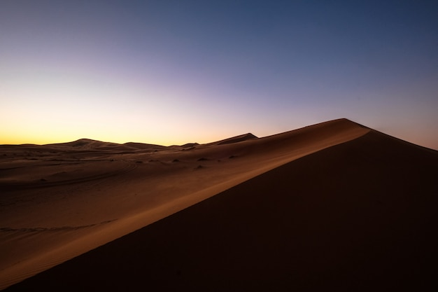Beautiful shot of sand dunes under a purple and blue sky