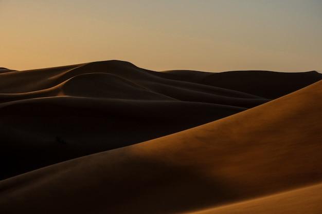Bello colpo delle dune di sabbia con il chiaro cielo