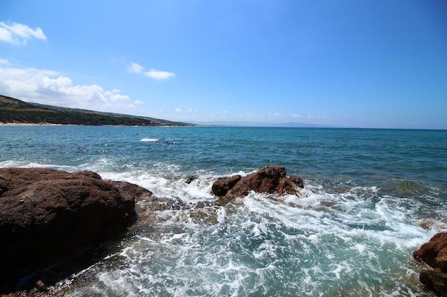 Bellissimo scatto del mare circondato da molte formazioni rocciose in una giornata di sole
