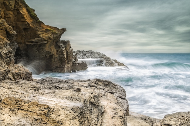 Beautiful shot of sea waves hitting the rocks on the seashore with a cloudy gray sky