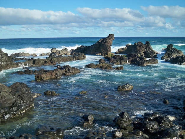 Beautiful shot of sea waves splashing to the rock formations in hawaii