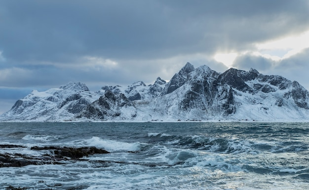 A beautiful shot of sea waves with a snowy mountain in the background