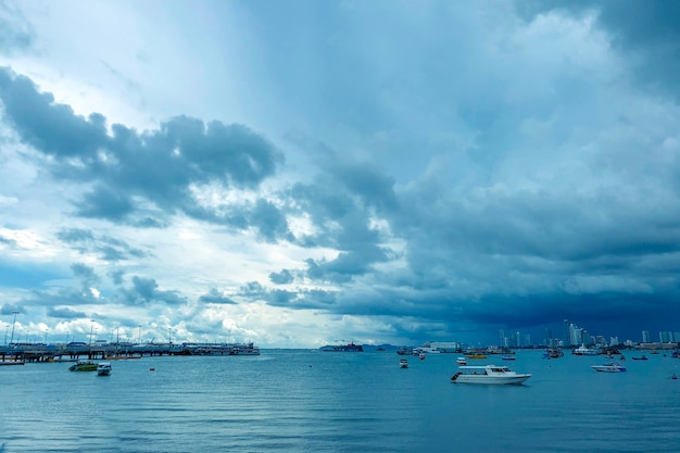 Beautiful shot of a sea with boats under a blue cloudy sky