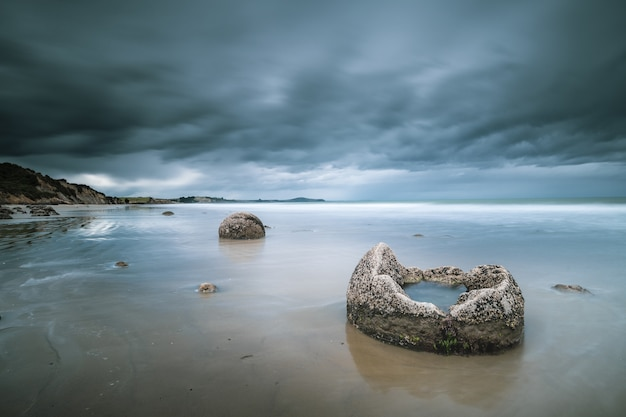 Beautiful shot of the sea with rocks and mountains in the distance under a blue cloudy sky