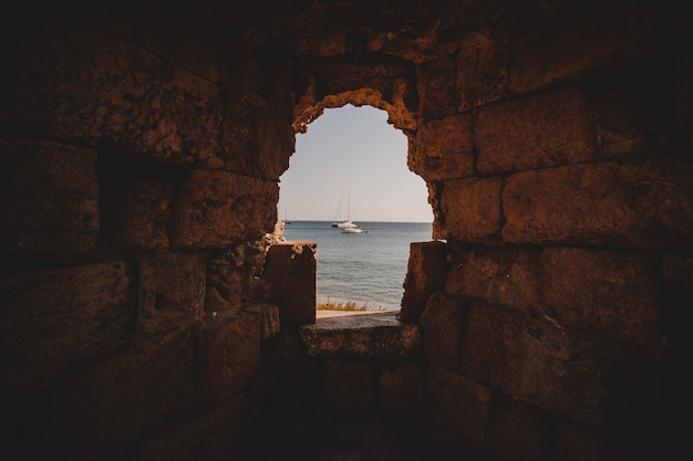 Beautiful shot of the sea with sailboats from the inside of a hole in a stone wall
