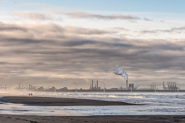 Beautiful shot of a sea with windmills and factory in the distance under a cloudy sky