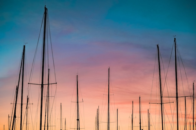 Beautiful shot of a silhouette of sailboat masts  at sunset