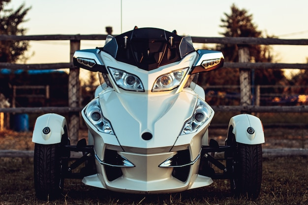 Beautiful shot of the silver sports quad bike in the field in front of a wooden fence