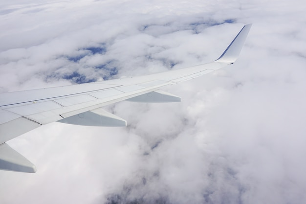 Beautiful shot of the sky full of clouds and an airplane wing from the plane window