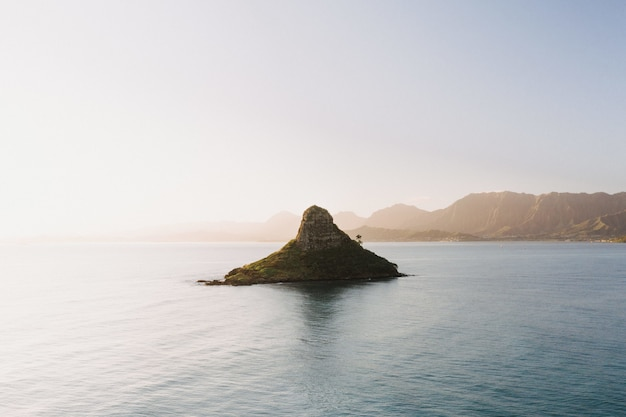 Beautiful shot of a small island in the center of the open sea with a scenery of sunrise