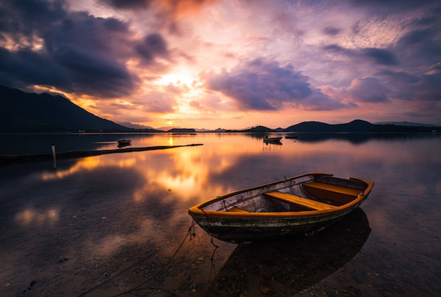 Beautiful shot of a small lake with a wooden rowboat in focus and amazing clouds in the sky