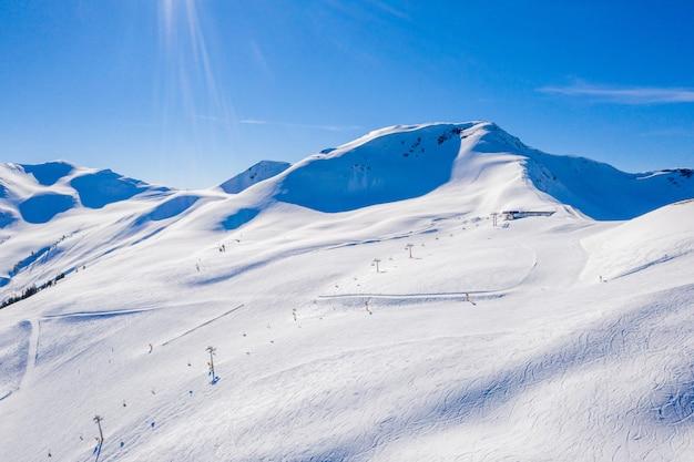 Bellissimo scatto di montagne innevate con aree sciistiche sulle loro piste sotto un cielo blu