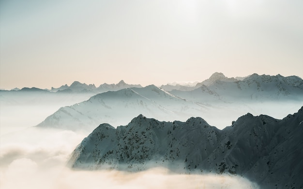 Beautiful shot of snowy mountain tops above the clouds with a clear sky