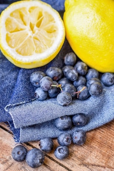 A beautiful shot of a squeezed lemon a full lemon and blueberries
