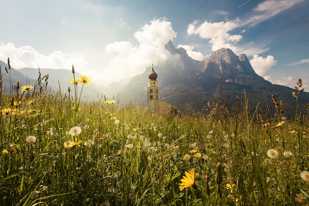 Beautiful shot of the st. valentin chapel surrounded with majestic mountains in italy
