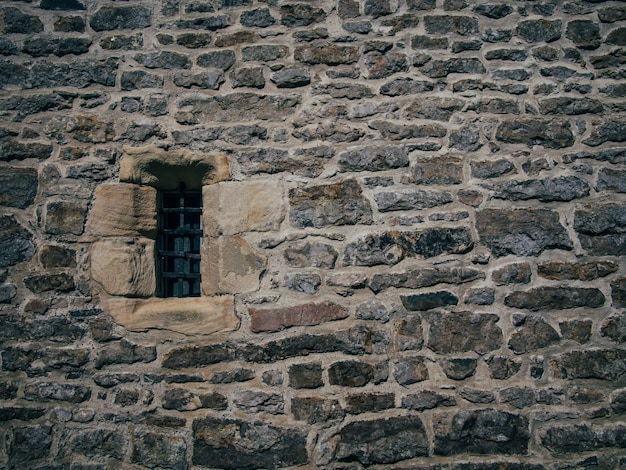 Beautiful shot of a stone brick old structure with a blocked small window