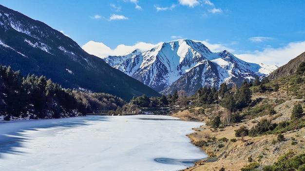 Bella ripresa di una vetta con un lago ghiacciato e un terreno con alberi e arbusti