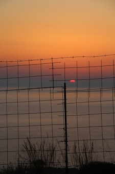 Beautiful shot of the sunset over the ocean behind the metal fence in crete