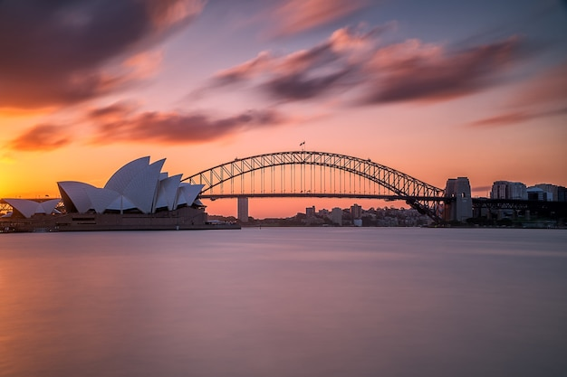 Beautiful shot of the sydney harbor bridge with a light pink and blue sky