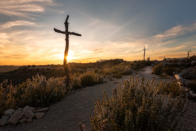A beautiful shot of tall wooden crosses in a deserted land at sunset