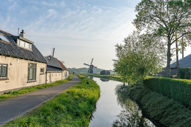 Beautiful shot of a water canal at the side of a narrow road with a windmill on a field