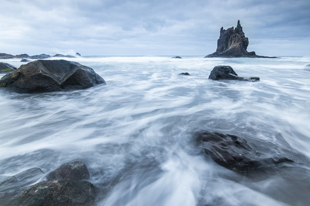 Beautiful shot of water flowing around large stones near the benijo rock on a cloudy day in spain