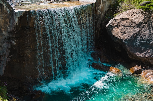 Beautiful shot of a waterfall near huge rock formations in pragelato, italy