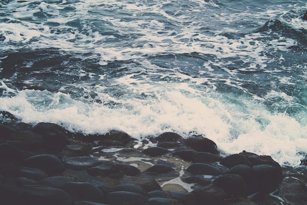 Beautiful shot of the waves of the ocean crashing on the stones in the shore
